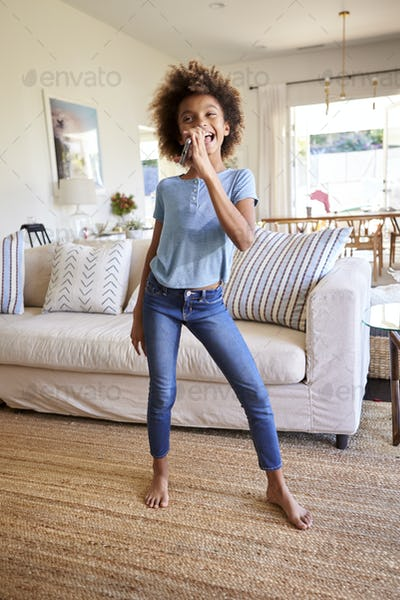 Pre-teen black girl dancing and singing in the living room at home using her phone as a microphone