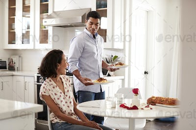 Young adult woman sitting at table in the kitchen and her partner serving a romantic meal