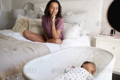 Young mother on her bed looking down at her three month old baby sleeping in his cot, close up