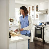 Millennial woman standing at worktop in the kitchen preparing food