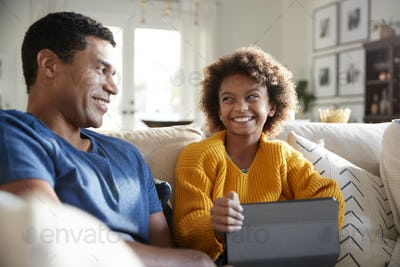 Close up of father and daughter sitting on sofa in the living room smiling at each other