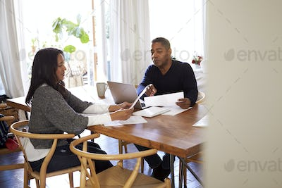 Man with laptop computer giving financial advice to a woman sitting at the table