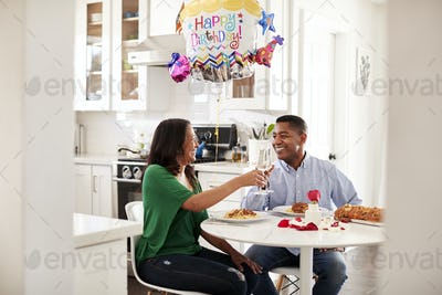 Black couple making a toast over a romantic birthday meal in their kitchen