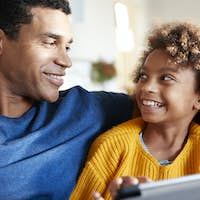 Close up of father and daughter using tablet computer, looking at each other smiling