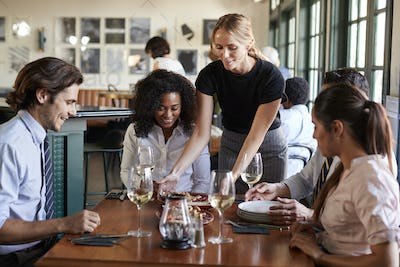 Waitress Serving Meal To Business Colleagues Sitting Around Restaurant Table
