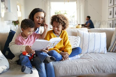 Close up of young mother sitting on a sofa in the living room reading a book to her two children