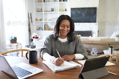Happy middle aged mixed race woman sitting at table in her dining room making notes, selective focus