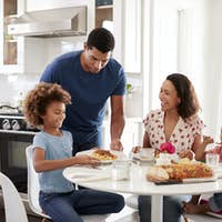 Young mother sitting at table in the kitchen with children, father serving them food