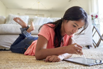 Teenage girl at home lying on the floor in the living room using tablet computer and stylus