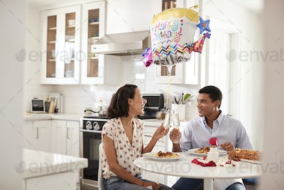 Couple sitting at the table in kitchen making a toast while eating a romantic birthday meal