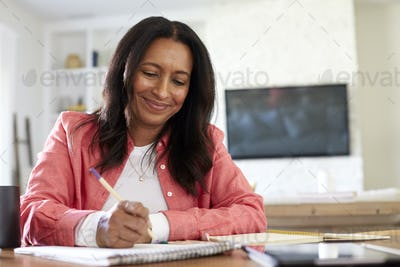 Smiling mixed race retired woman sitting at a table writing in her dining room, close up, low angle