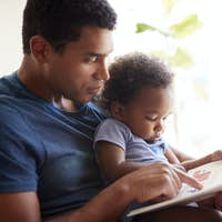 Close up of young adult black father reading a book with his two year old son