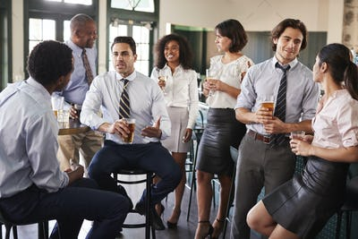 Business Colleagues Meeting For After Works Drinks In Bar