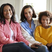 Three generation family female family group sitting on a sofa in the living room smiling to camera