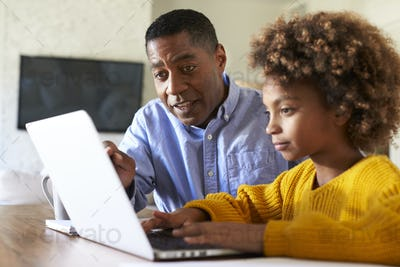 Black girl using a laptop computer sitting at table in the dining room with her home tutor