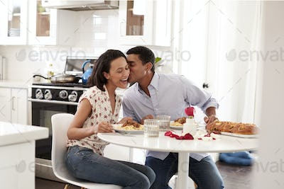 Young couple having romantic meal sitting at table in the kitchen, selective focus