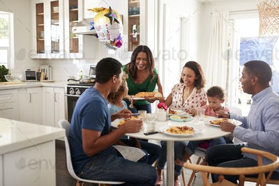 Mixed race three generation family sitting together at the kitchen table