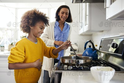 Girl standing in the kitchen preparing food with her mother, side view