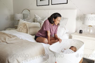 Young adult mother sitting on her bed looking down at her three month old baby sleeping in his cot