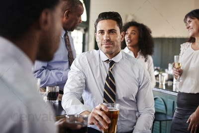 Two Businessmen Meeting For After Works Drinks In Bar
