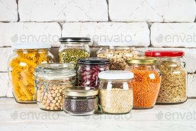 Cereals, Legumes, and beans in glass jars on white kitchen table