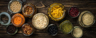 Cereals, Legumes, and beans in glass jars on dark wooden table