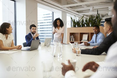 Businesswoman Standing Giving Presentation To Colleagues In Modern Open Plan Office