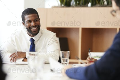 Two Businessmen Sitting Around Table Meeting In Modern Open Plan Office