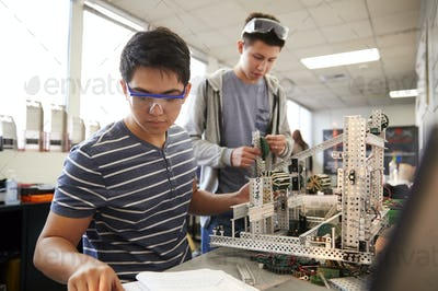 Two Male College Students Building Machine In Science Robotics Or Engineering Class