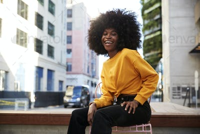 Young black woman with afro hair sitting on a chair in the street laughing to camera