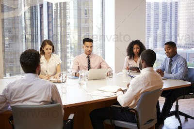 Group Of Business Professionals Meeting Around Table In Modern Office