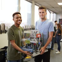 Portrait Of Two Male University Students Carrying Machine In Science Robotics Or Engineering Class