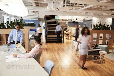 Interior View Of Modern Open Plan Office With Blurred Businessmen And Businesswomen