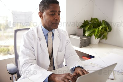 Male Doctor Wearing White Coat In Office Sitting At Desk Working On Laptop