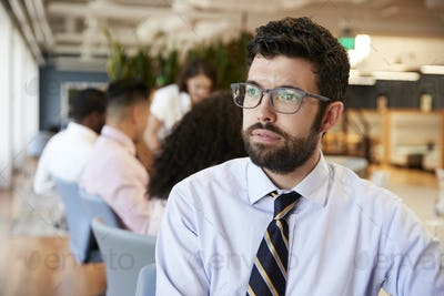 Businessman In Modern Office With Colleagues Meeting Around Table In Background