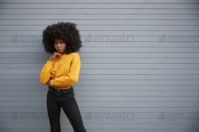 Hip young black woman standing against grey security shutters, head on hand, looking to camera