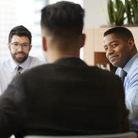 Three Businessmen Sitting Around Table Meeting In Modern Open Plan Office