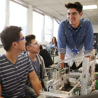 Teacher With Two Male College Students Building Machine In Science Robotics Or Engineering Class