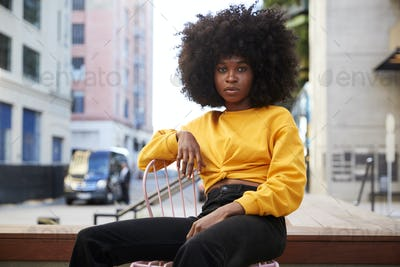 Young black woman with afro hair and yellow top sitting on a chair in the street looking to camera