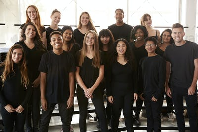 Portrait Of Male And Female Students Singing In Choir At Performing Arts School