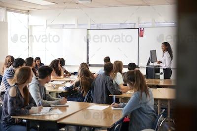 Female High School Teacher Standing By Interactive Whiteboard Teaching Lesson