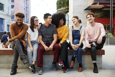 Six young adult friends sitting in a row on a bench in the street looking at each other, full length