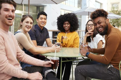 Six trendy millennial friends sitting drinking outside a cafe, turning and smiling to camera