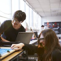 Two Male College Students Work On Computer Controlled Rig In Science Robotics Or Engineering Class