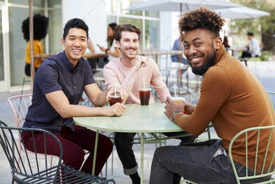 Three millennial male friends talking over cold brews outside a cafe in a city street turn to camera