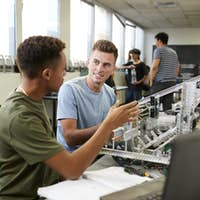 Two Male University Students Building Machine In Science Robotics Or Engineering Class