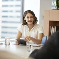 Businesswoman With Digital Tablet Sitting At Table Meeting With Colleagues In Modern Office