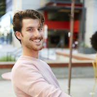 Millennial white hipster man sitting outside a cafe in the street, turns smiling to camera, close up