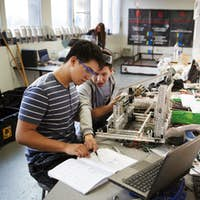 Two Male College Students With Laptop Building Machine In Science Robotics Or Engineering Class