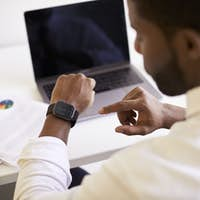 Businessman Working On Laptop At Desk In Modern Office Checking Data On Smart Watch